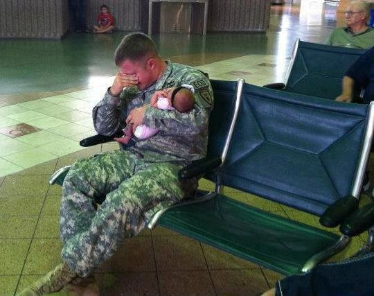 A soldier holding his newborn baby before being deployed
